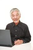 Hombre japonés mayor que usa el ordenador portátil Imágenes de archivo libres de regalías