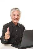 Hombre japonés mayor que usa el ordenador portátil Fotografía de archivo libre de regalías