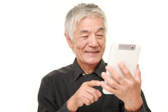 Hombre japonés mayor que usa la tableta Foto de archivo libre de regalías