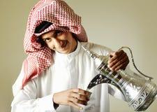 Hombre joven árabe que vierte un café Imagen de archivo libre de regalías
