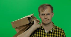 Hombre joven aburrido en el fondo dominante de la croma verde de la pantalla con los bolsos de compras foto de archivo
