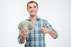 Hombre joven acertado alegre que sostiene el dinero y que muestra los pulgares para arriba Fotografía de archivo libre de regalías