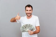 Hombre joven acertado alegre que sostiene el dinero y que muestra los pulgares para arriba Fotografía de archivo
