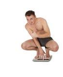 Hombre joven acertado en escala Foto de archivo libre de regalías