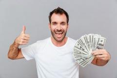 Hombre joven acertado feliz que sostiene el dinero y que muestra los pulgares para arriba Imagen de archivo