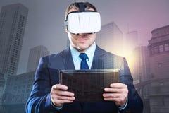 Hombre joven acertado que trabaja con las auriculares y la tableta de VR fotos de archivo libres de regalías