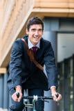Hombre joven activo que sonríe mientras que monta la bicicleta para uso general a su wor Fotos de archivo libres de regalías