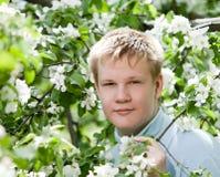 Hombre joven, adolescente que se coloca cerca de la manzana Imagen de archivo
