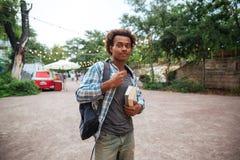 Hombre joven africano hermoso con la mochila y los libros Fotos de archivo