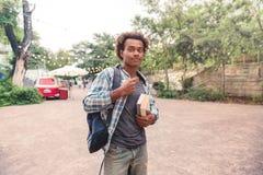 Hombre joven africano hermoso con la mochila y los libros Foto de archivo