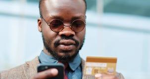 Hombre joven afroamericano en gafas de sol que hace compras en línea con la tarjeta de crédito usando el teléfono elegante en la  almacen de video