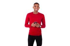 Hombre joven afroamericano que envía un mensaje de texto en su smartph Imagen de archivo libre de regalías