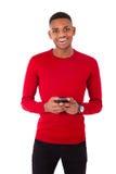 Hombre joven afroamericano que envía un mensaje de texto en su smartph Foto de archivo libre de regalías