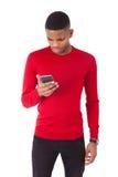 Hombre joven afroamericano que envía un mensaje de texto en su smartph Fotos de archivo