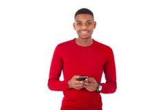 Hombre joven afroamericano que envía un mensaje de texto en su smartph Fotografía de archivo libre de regalías