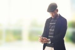Hombre joven afroamericano que usa smartphone Imágenes de archivo libres de regalías