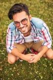 Hombre joven agachado en un campo de hierba Foto de archivo