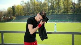 Hombre joven agotado que limpia el sudor con la toalla de su frente despu?s de ejercitar Agua potable de la deportista cansada y metrajes
