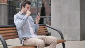 Hombre joven al aire libre emocionado para el éxito en smartphone metrajes