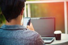 Hombre joven al aire libre en la terraza con el funcionamiento del ordenador portátil y del smartphone fotografía de archivo libre de regalías