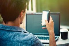 Hombre joven al aire libre en la terraza con el funcionamiento del ordenador portátil y del smartphone fotos de archivo libres de regalías