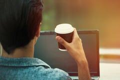 Hombre joven al aire libre en la terraza con el ordenador portátil y la taza de café foto de archivo