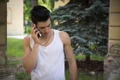 Hombre joven al aire libre que habla en el teléfono celular Imagenes de archivo