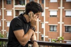 Hombre joven al aire libre que habla en el teléfono celular Fotos de archivo libres de regalías
