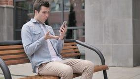 Hombre joven al aire libre trastornado por la pérdida mientras que usa smartphone almacen de metraje de vídeo