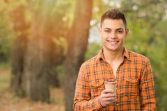 Hombre joven alegre con café en parque en otoño Fotografía de archivo