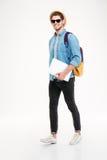 Hombre joven alegre con la mochila que camina y que sostiene el ordenador portátil Foto de archivo libre de regalías