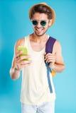 Hombre joven alegre con la mochila usando el teléfono móvil Foto de archivo libre de regalías