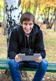 Hombre joven alegre con la tableta Fotos de archivo