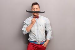Hombre joven alegre con un bigote falso enorme Fotos de archivo libres de regalías