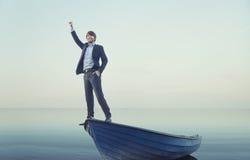 Hombre joven alegre en el barco minúsculo Imagen de archivo libre de regalías
