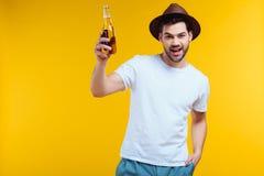 hombre joven alegre en el sombrero que sostiene la botella de cristal de bebida del verano y que sonríe en la cámara fotografía de archivo