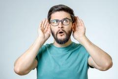 Hombre joven alegre en llevar a cabo la mano cerca del oído Imágenes de archivo libres de regalías