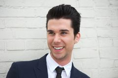 Hombre joven alegre en traje de negocios que sonríe al aire libre Fotos de archivo