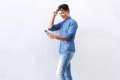Hombre joven alegre que camina y que lee el texto en el teléfono celular Fotografía de archivo