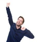 Hombre joven alegre que celebra con los brazos aumentados Fotos de archivo libres de regalías