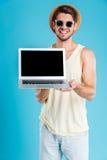 Hombre joven alegre que coloca y que sostiene el ordenador portátil de la pantalla en blanco Fotografía de archivo