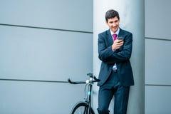 Hombre joven alegre que comunica en el teléfono móvil mientras que espera o fotografía de archivo