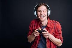 Hombre joven alegre que juega a los videojuegos Imagen de archivo