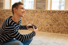 Hombre joven alegre que juega a un juego Imagen de archivo