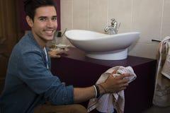Hombre joven alegre que limpia el cuarto de baño Imágenes de archivo libres de regalías