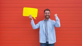 Hombre joven alegre que lleva a cabo una nube del diálogo o un discurso amarillo rectangular de la burbuja en fondo rojo almacen de metraje de vídeo