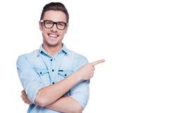 Hombre joven alegre que señala el espacio de la copia Fotografía de archivo