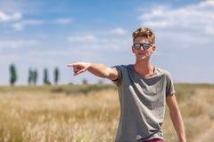 Hombre joven alegre que señala en algo Un inconformista elegante en un fondo natural Concepto libre de la forma de vida Copie el  Foto de archivo