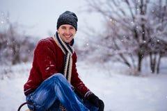 Hombre joven alegre que se divierte en un trineo en invierno Fotos de archivo libres de regalías