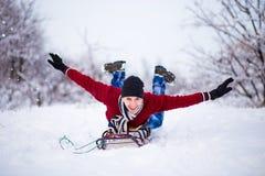 Hombre joven alegre que se divierte en un trineo en invierno Foto de archivo